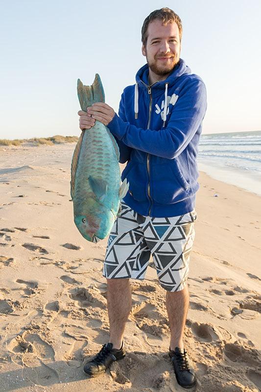 Tom s čerstvou rybou na pláži v Ománu