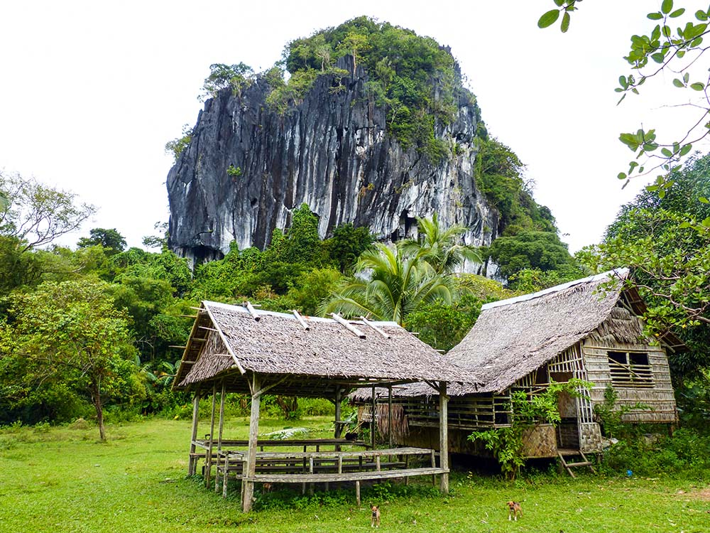 Bamboo house next to rock cave
